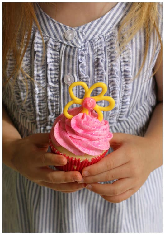 a girl holding a pink cupcake