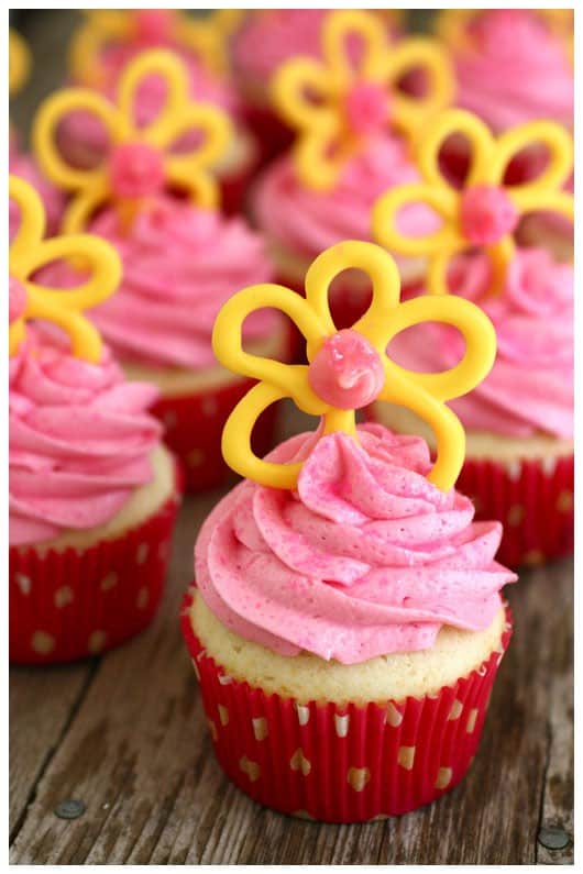 cupcakes with pink frosting and yellow candy flowers