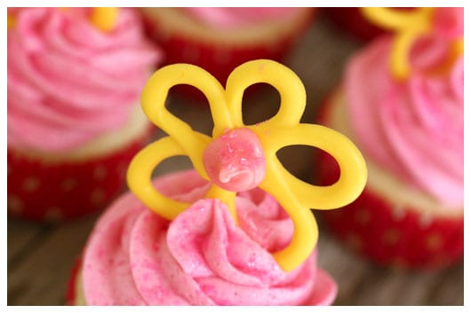 a yellow candy flower on top of a pink cupcake