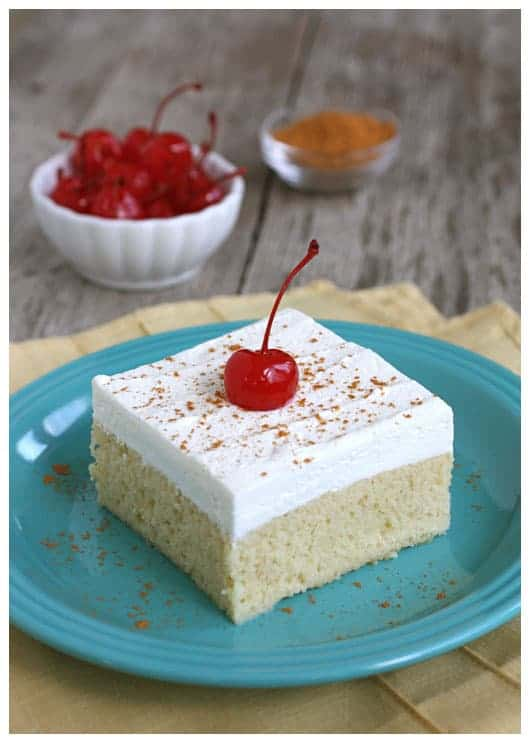 a slice of tres leches cake with a cherry on top