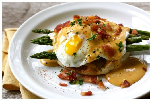 a white plate with eggs benedict and bbq hollandaise sauce
