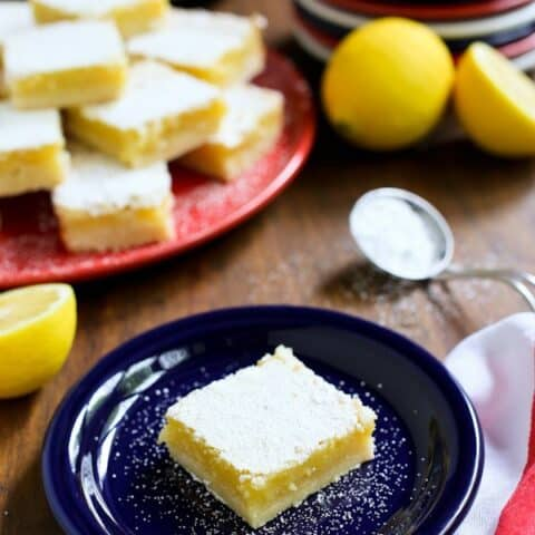 A Lemon Bar on a blue plate with a stack of more lemon bars behind it