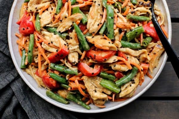 Salad with chicken, green beans, and red pepper in a white bowl