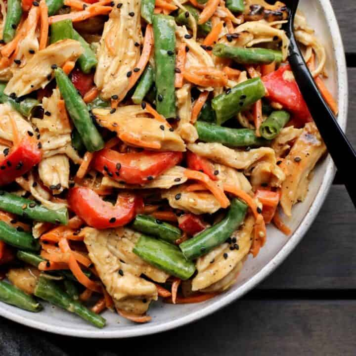 Salad with chicken, beans, and red peppers in a peanut butter dressing, in a bowl