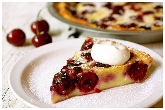 a slice of cherry clafouti topped with whipped cream