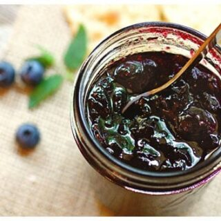 Top view of a jar of blueberry jam with a spoon