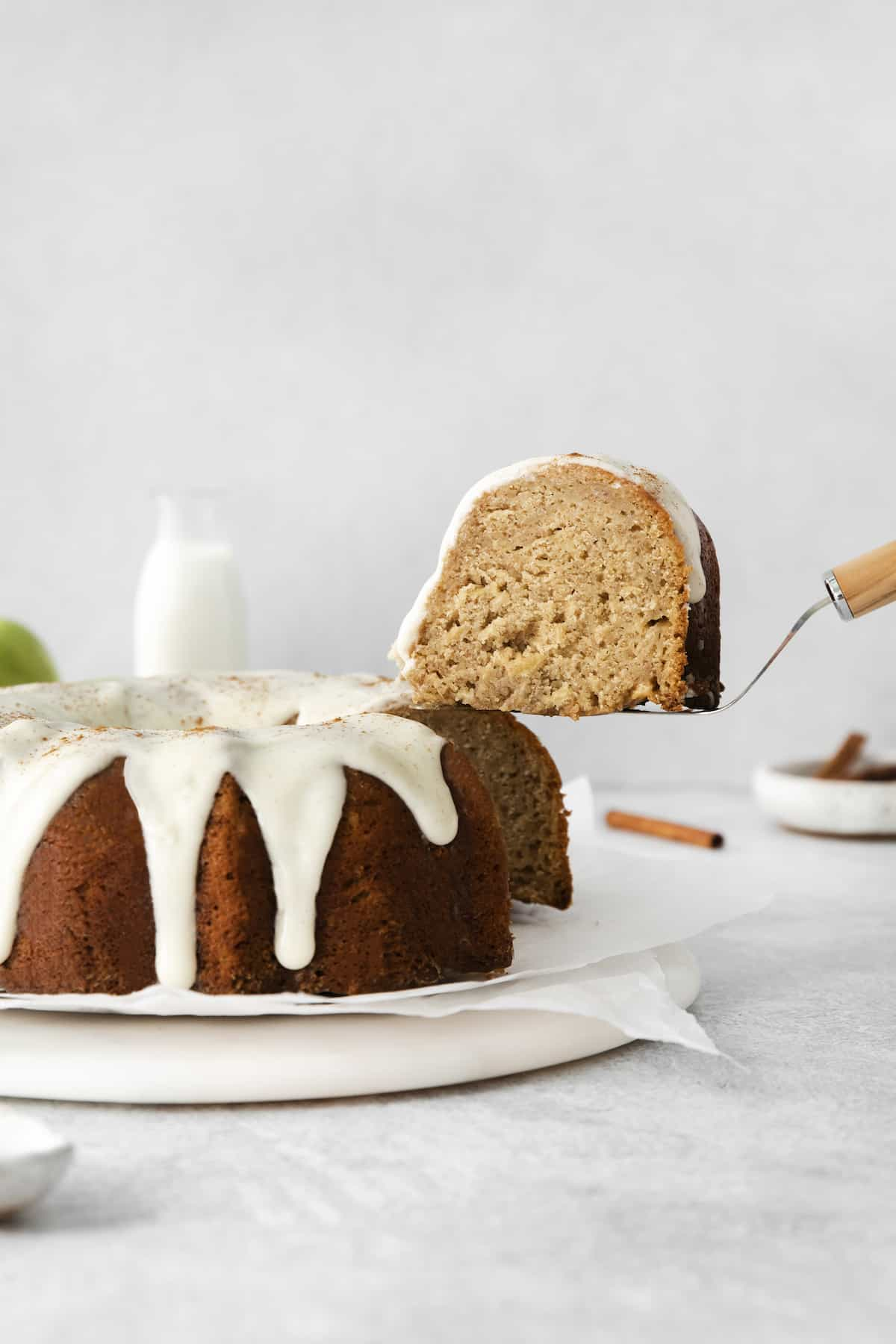 An apple bundt cake with a slice on a serving utensil