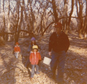 three girls with their dad on a walk
