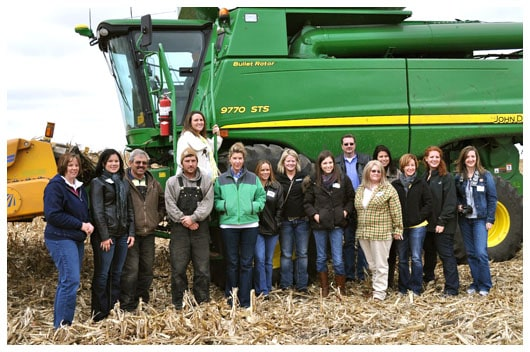 a group of people in front of a john deer combine