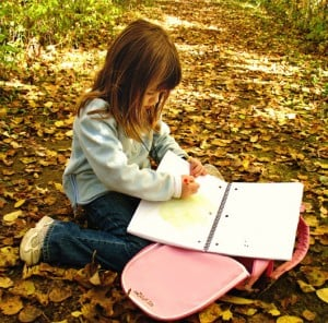 a girl coloring in a notebook
