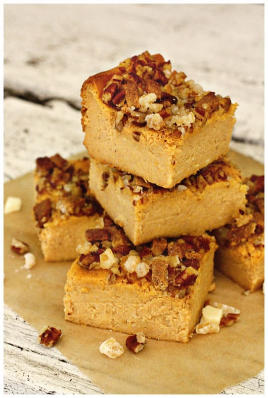 pumpkin cheesecake bars topped with nuts and ginger