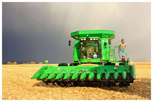 A Man Standing on a Bright Green Combine