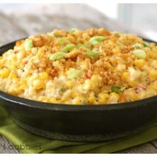 a black bowl of cheesy corn