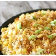 Cheesy scalloped corn in a black bowl
