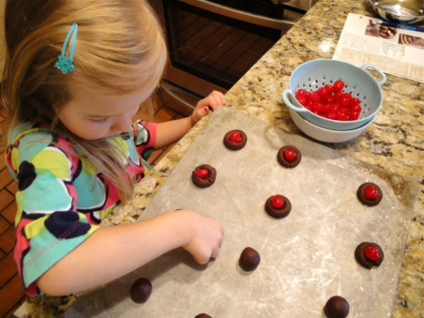 a young girl assembling cherry cookies
