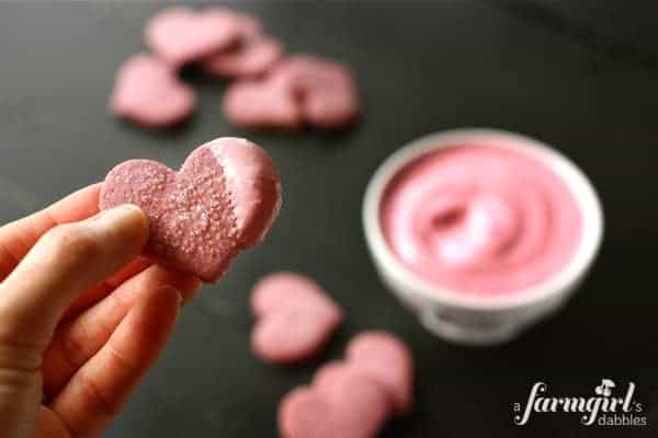a heart shaped cookie dipped in pink frosting