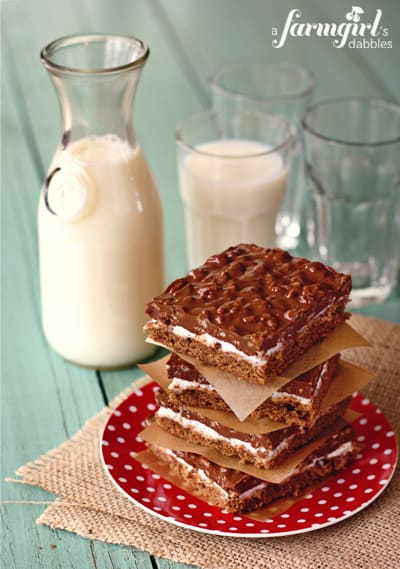 a stack of chocolate crispy bars and a pitcher of milk