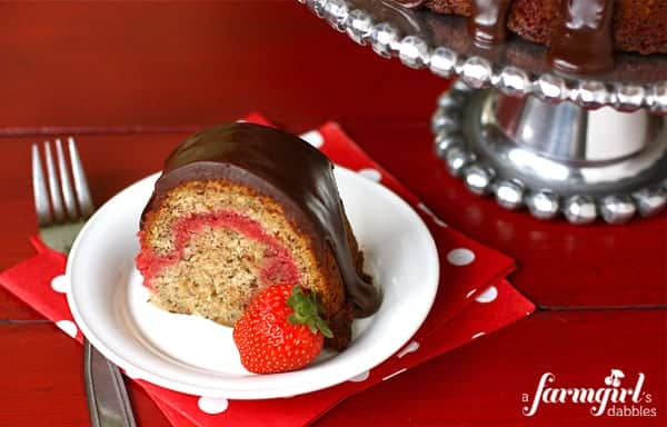 Slice of banana split bundt cake with chocolate frosting and a fresh strawberry on a round white plate