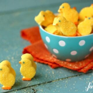 Yellow marshmallow chicks sprinkled with sugar in a blue bowl