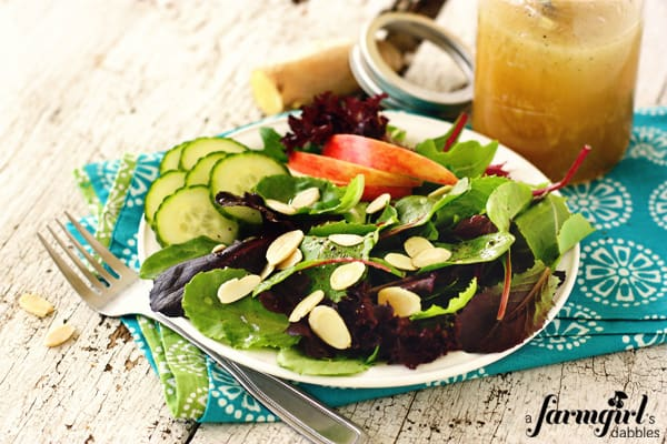 a salad with almonds, cucumbers, and dressing