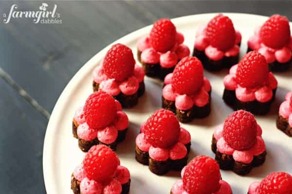 flower shaped brownies with frosting and raspberries