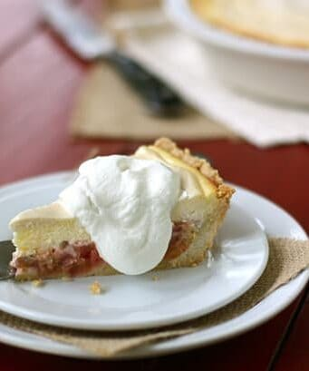 a slice of rhubarb cheesecake pie topped with whipped cream