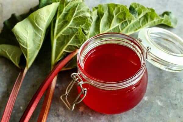 fresh rhubarb and a jar of homemade rhubarb syrup