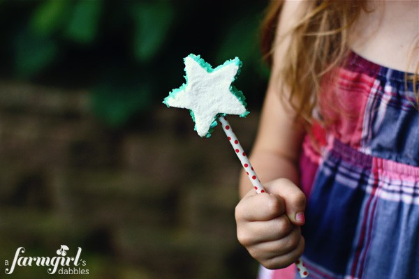 a girl holding a marshmallow pop