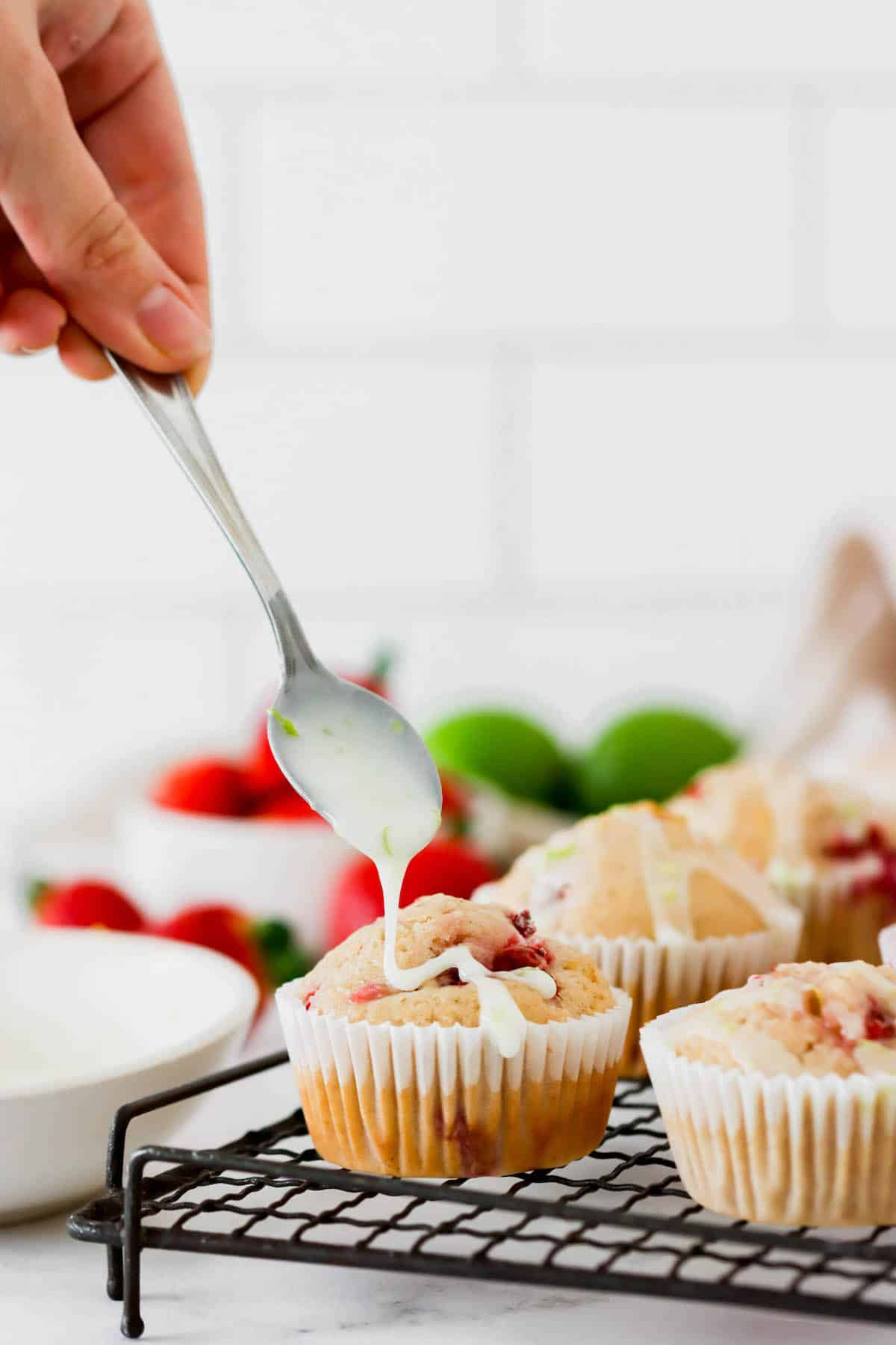 Lime glaze being drizzled over strawberry muffins