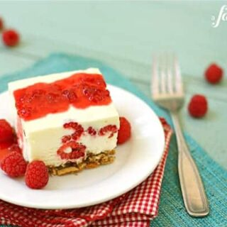 frozen white chocolate dessert on a pretzel crust with fresh raspberries