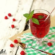 a glass cup of iced tea with fresh raspberries