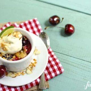 a white ramekin with cherry crumble and whipped cream