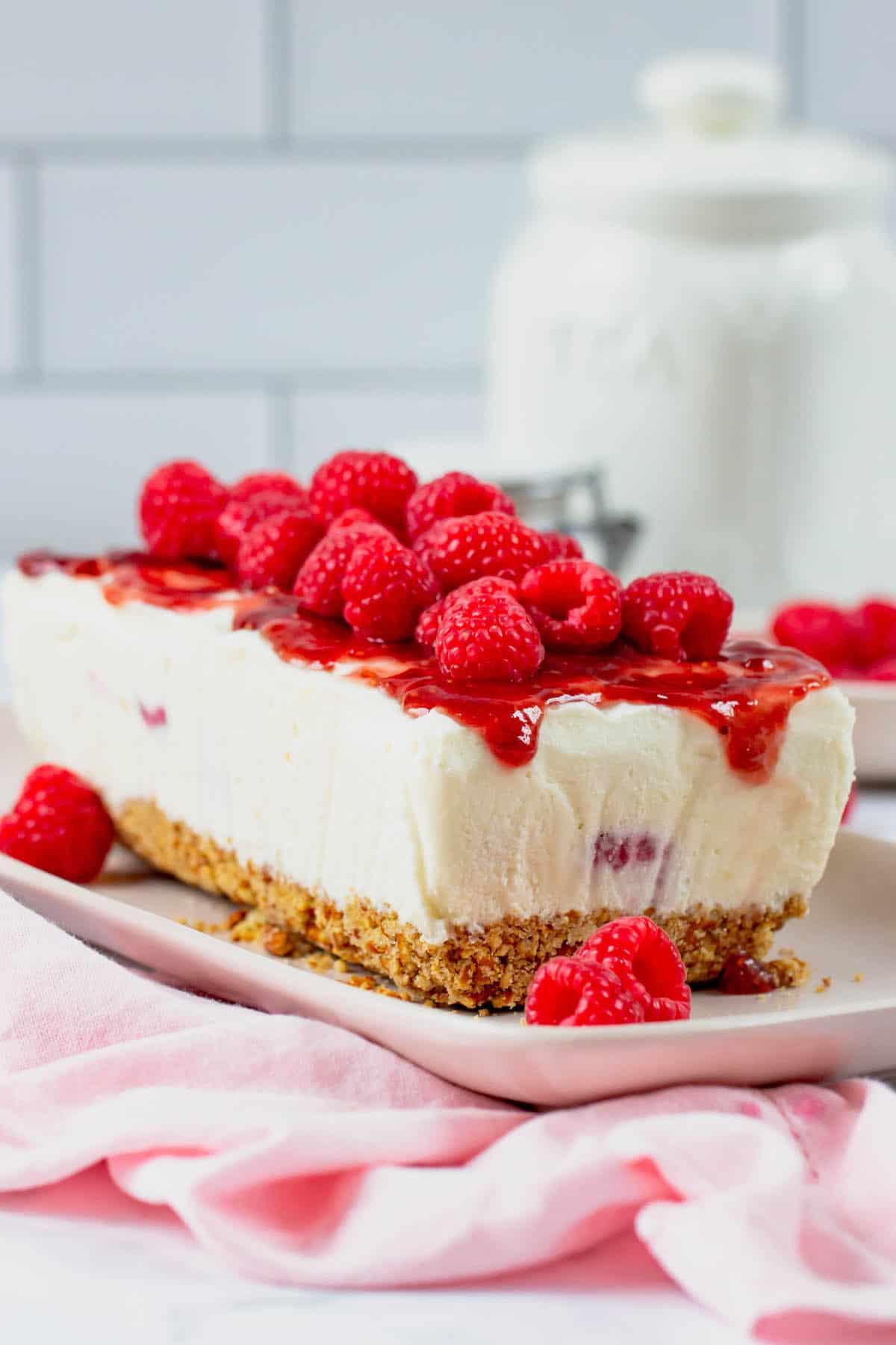 Frozen white chocolate raspberry dessert topped with fresh raspberries