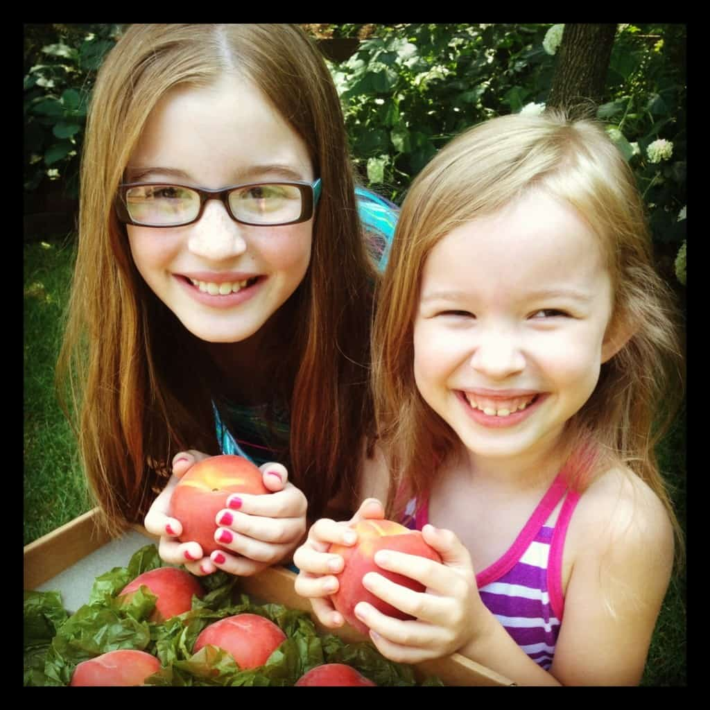 two girls holding peaches