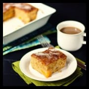 a slice of peach cake with a cup of coffee
