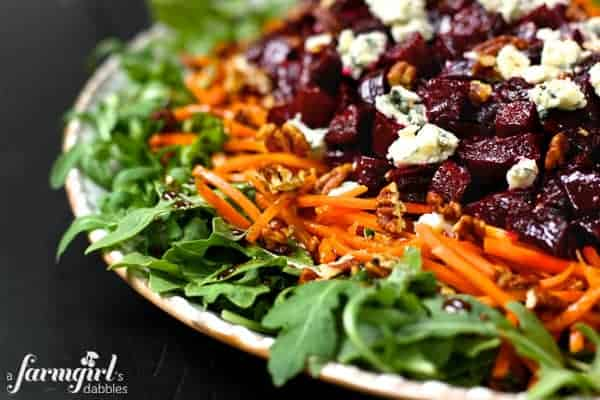 an arugula salad with carrots and roasted beets