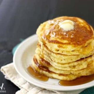A stack of buttermilk pancakes on a white plate with butter and maple syrup
