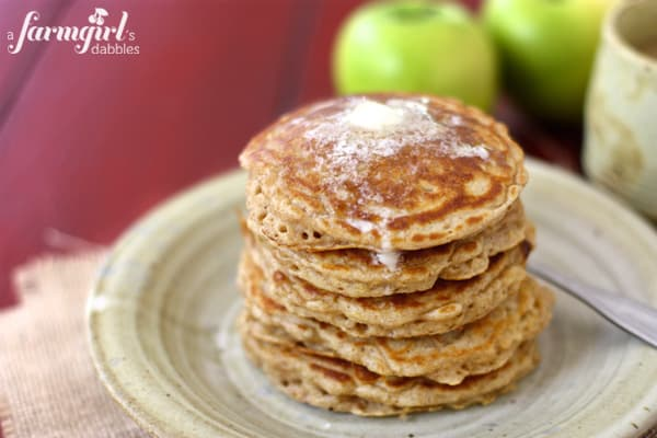Apple Pancakes Stacked on a Plate with Melty Butter on Top