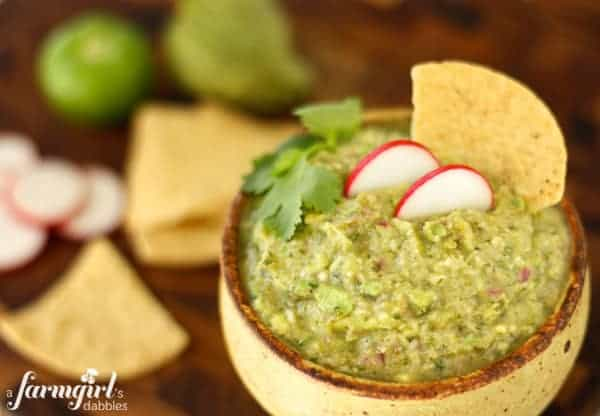 a pottery bowl of guacamole with tortilla chips