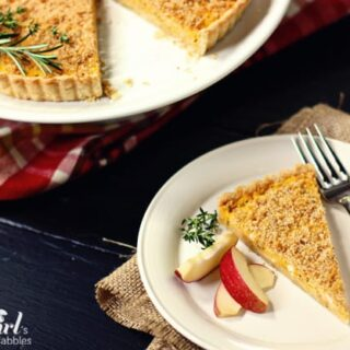A slice of butternut squash tart on a white plate with apple slices