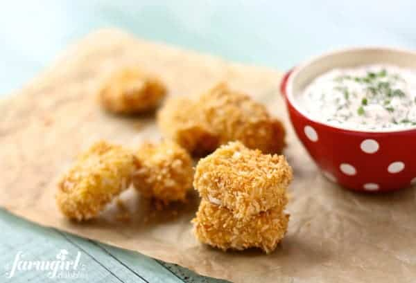 Baked chicken nuggets on parchment paper with a bowl of homemade ranch dip