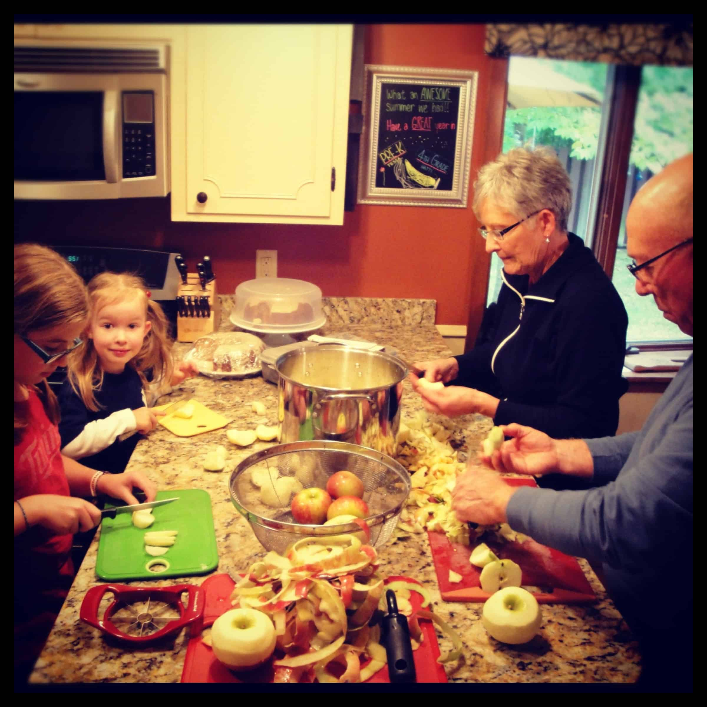 family making applesauce together in kitchen