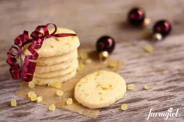 A stack of shortbread cookies with pieces of candied ginger wrapped in plum-colored ribbon
