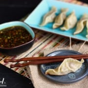 a plate of potstickers with a soy dipping sauce