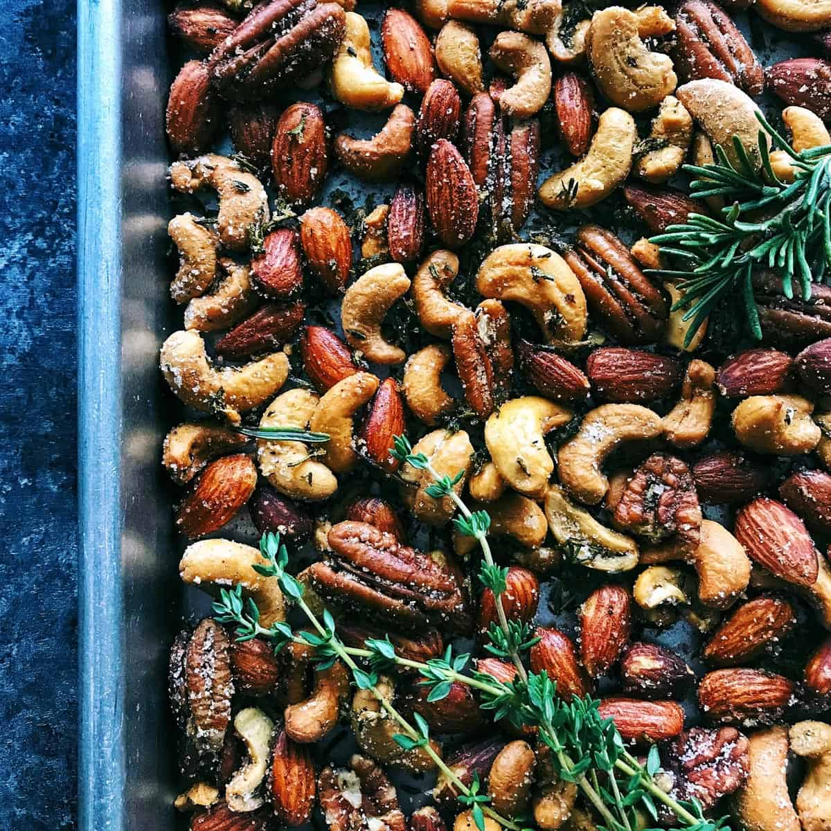 nuts on a rimmed pan with spices and herbs