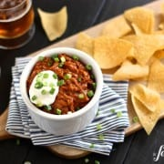 a white dish of Cheesy Beef Taco Dip with tortilla chips
