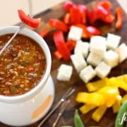 Bagna Cauda dip with sun-dried tomatoes in a warming pot with vegetables and bread cubes for dipping