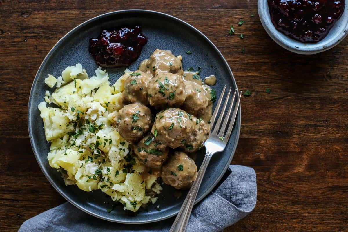 Swedish meatballs and gravy on a plate with a fork.
