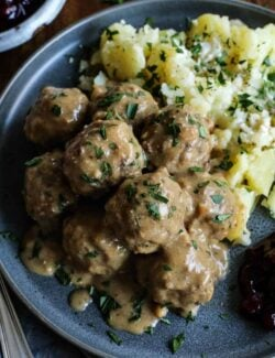 Swedish meatballs with gravy on a gray plate, with potatoes and lingonberry jam