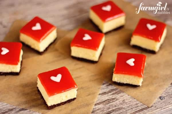 white chocolate cheesecake squares topped with strawberry glaze and a white heart